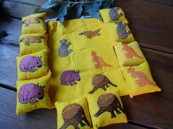 Ten little cotton cushions with five pairs of appliquéd Australian animals are neatly presented in a yellow cotton appliquéd drawstring bag.  Made by the artisans at Artisans Effort a fair trade group in India