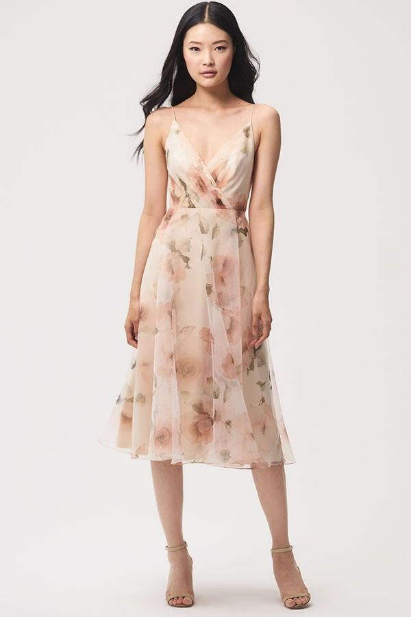 Jenny Yoo 2018 Bridesmaids, the short floral printed Sabrina dress features a surplice bodice with delicate spaghetti straps for a feminine silhouette. The taffeta circle skirt hits at midi tea length and billows out to create movement. V Neck. This dress is fully lined with a center back seam. Perfect for a cocktail event, garden, or summer wedding. Shown in Blush Multi, available in Black Multi.