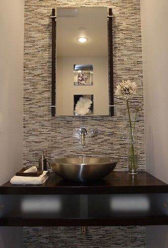 Powder room featuring Erin Adams glass mosaic tile on wall (from Ann Sacks). Kohler stainless steel vessel sink  wall mounted faucet. Espresso stained Alder wood custom floating counter with sliding frosted glass panels to conceal storage.