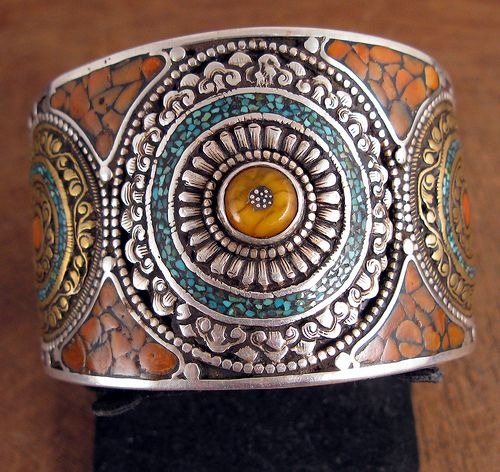 Nepal |  Tibetan bracelet made from silver with some gold plating with Turquoise, amber and Coral set in wax.