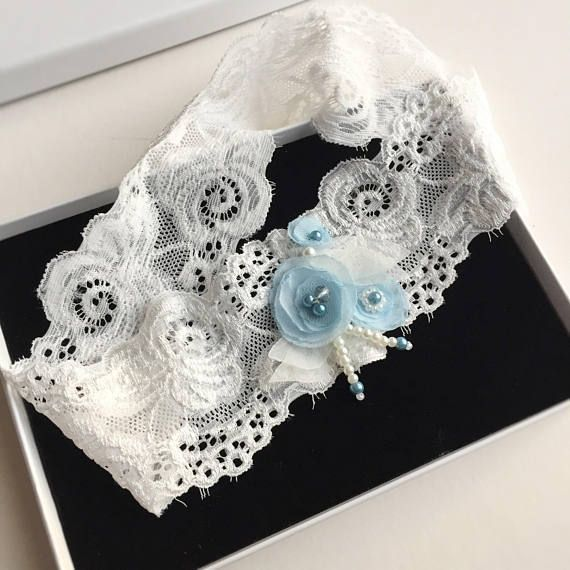 A beautiful, non-frilly lace garter, with a light ivory elastic lace base, and three sky blue fabric flowers, flanked by delicate ivory voile leaves and embellished with beads and a smokey blue crystal. This bridal garter is perfect as a Something Blue garter to wear and have in your