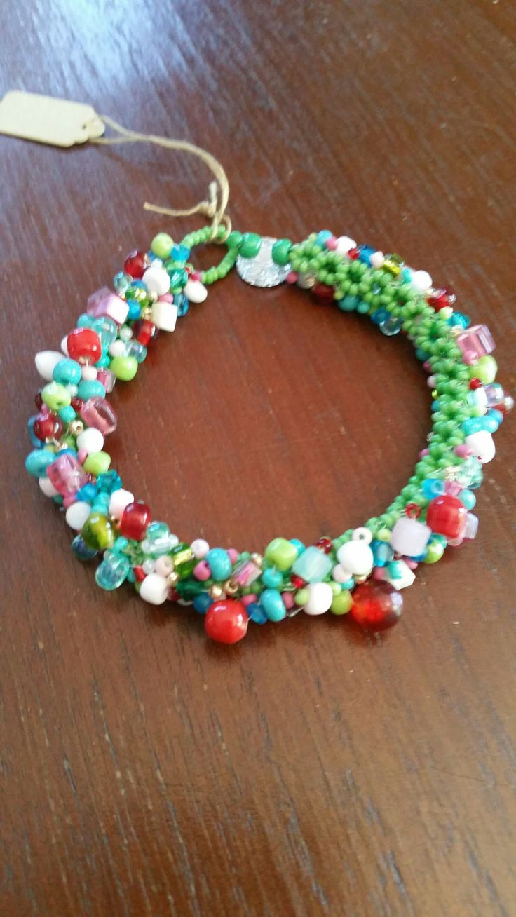 Square stitch bracelet with red/pink/green and aqua embelishments.
