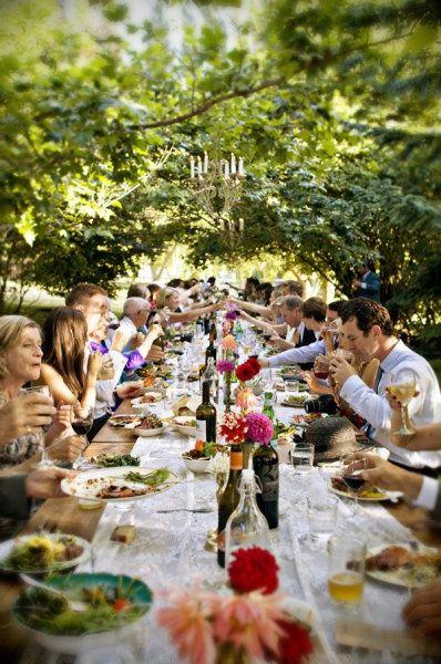 Family Style Wedding Dinner. Bottles holding a few blooms leave room for serving platters...