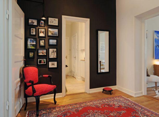 czarna ściana,czerwony fotel,ramki,galeria zdjęć w korytarzu,turecki dywan,wąski przedpokój,biały przedpokój,korytarz,jak urzadzić wąski korytarz,biale ściany,skandynawski styl,nowoczesne mieszkanie,dekoracja holu,dekoracje do przedpokoju,typografie,czarny chodnik,dywan w przedpokoju,biała podłoga