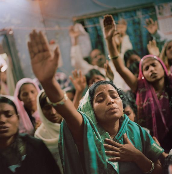 ODISHA, REPUBLIC OF INDIA | India's 27 million Christians credit the Apostle Thomas with bringing Jesus' message there—and dying for it. Adhering to a faith that challenges the Hindu caste system can still be risky: In 2008 extreme nationalists killed at least 60 Christians and displaced some 60,000 in Odisha state. Worshippers there still gather, but less openly, in a pastor's home (above).    -- Photograph by Lynn Johnson