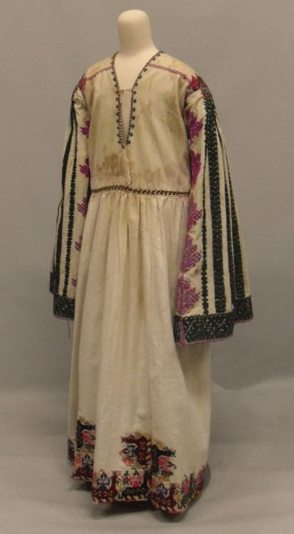 """Skolopendrato"". Cotton chemise. H. 1.32 m. Astypalaia, Dodecanese, Greece, 1870. Peloponnesian Folklore Foundation Collection, Nafplion. 1985.6.83. ""Skolopendrato"". Long-sleeved, round neck, off-white woven cotton chemise with strips of embroidery..."