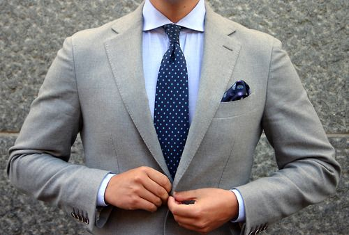 Groomsmen: Light grey suit, light blue dress shirt, and navy polka-dot tie with navy paisley pocket square. With ivory bout with gold ribbon and maybe a small blue flower.