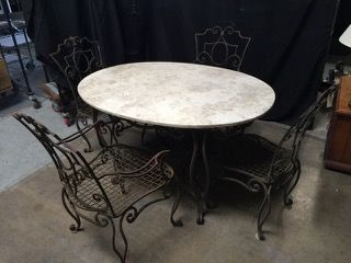 VINTAGE PATINATED IRON OUTDOOR PATIO TABLE AND CHAIRS SET WITH TRAVERTINE TOP. THE SET HAS DOUBLE SCROLLED LEGS AND ARMS WITH WOVEN METAL SEATS. TABLE MEASURES 29H X 49L X 36W AND THE CHAIRS (TWO CAPTAIN) MEASURE 36 INCHES HIGH.