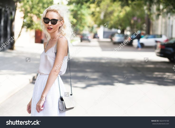 Young beautiful blonde woman in light dress with clutch and sun glasses posing outside with wooden wall in background. Fashion accessories. Streetstyle summer spring photo