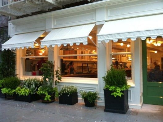 love the scalloped awnings, as well as the square planters. (round boxwood, or is it rosemary?)