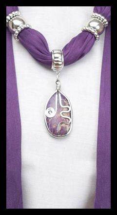 Fashion and Jewelry all in one accessory. This beautiful scarf is adorned with a earth elements pendant and overlaid with a silver swirl