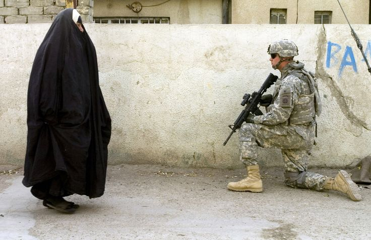 A local woman passes by US Army soldier as he pulls security during a patrol in the Graya'at area of Baghdad's Adhamiyah District 2007 [2229 x 1446]