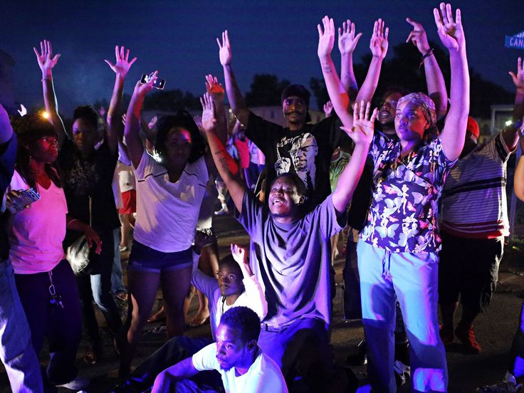 "Some protesters near the Ferguson Police Department chanted ""Don't shoot me!"" and held their hands in the air after the fatal shooting of Michael Brown by police in Ferguson, Mo"