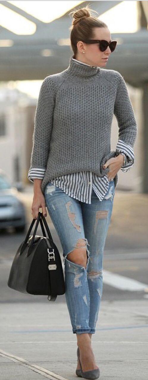 Grijze pull-over in combinatie met gestreept overhemd en ripped jeans.