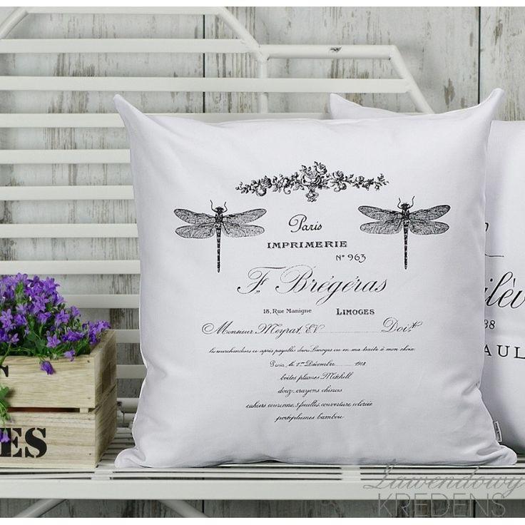 Białe poduszki z ważkami i napisami po francusku.