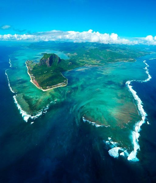 An Underwater Waterfall? What you're witnessing, that looks like an underwater waterfall, is actually sand from the shores of Mauritius being driven via ocean currents off of that high, coastal shelf, and down into the darker ocean depths off the southern tip of the island.