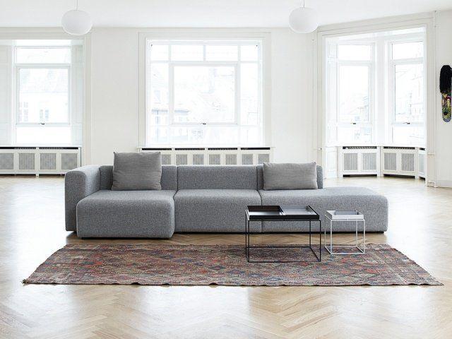 canapé d'angle modulable et convertible en couleur grise avec une table basse