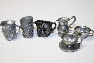 Pewter mugs with scary faces for your doll's beer drinking pleasure from the White Elephant Sale.