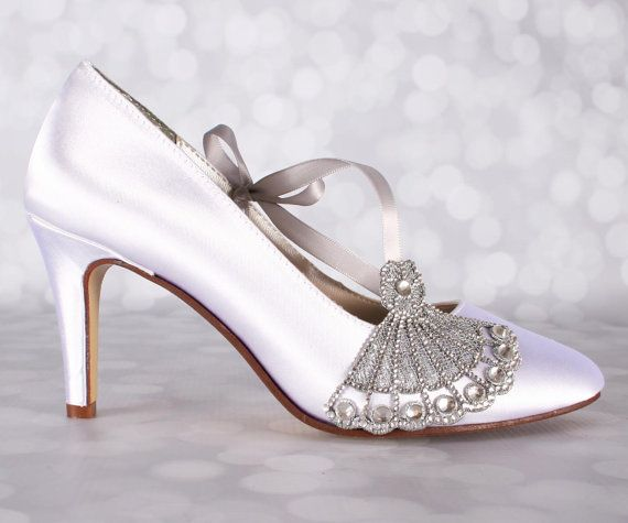 Ces chaussures de mariage assez blanc sont juste la bonne quantité d'éclat pour votre journée de mariage. Conçus pour chaque mariée sur mesure, ces talons mesurent 2 3/4(mesurée comme indiqué ici: http://www.customweddingshoe.com/about-ellie-wren/heel-height-measurement/) et sont présentés ici en blanc, avec un applique de cristal d'argent sur le gros orteil et une ceinture de ruban en satin argent décentrée sur le côté de la chaussure.  Couleur personnalisée :  Pour changer la couleur des…