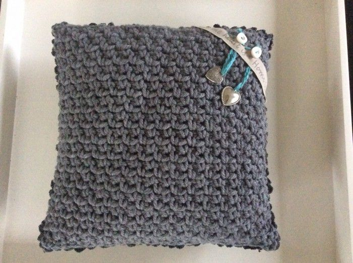 Stoer grijs gehaakt kussen in granietsteek, opgesierd met band en hartjes (makkelijk eraf te