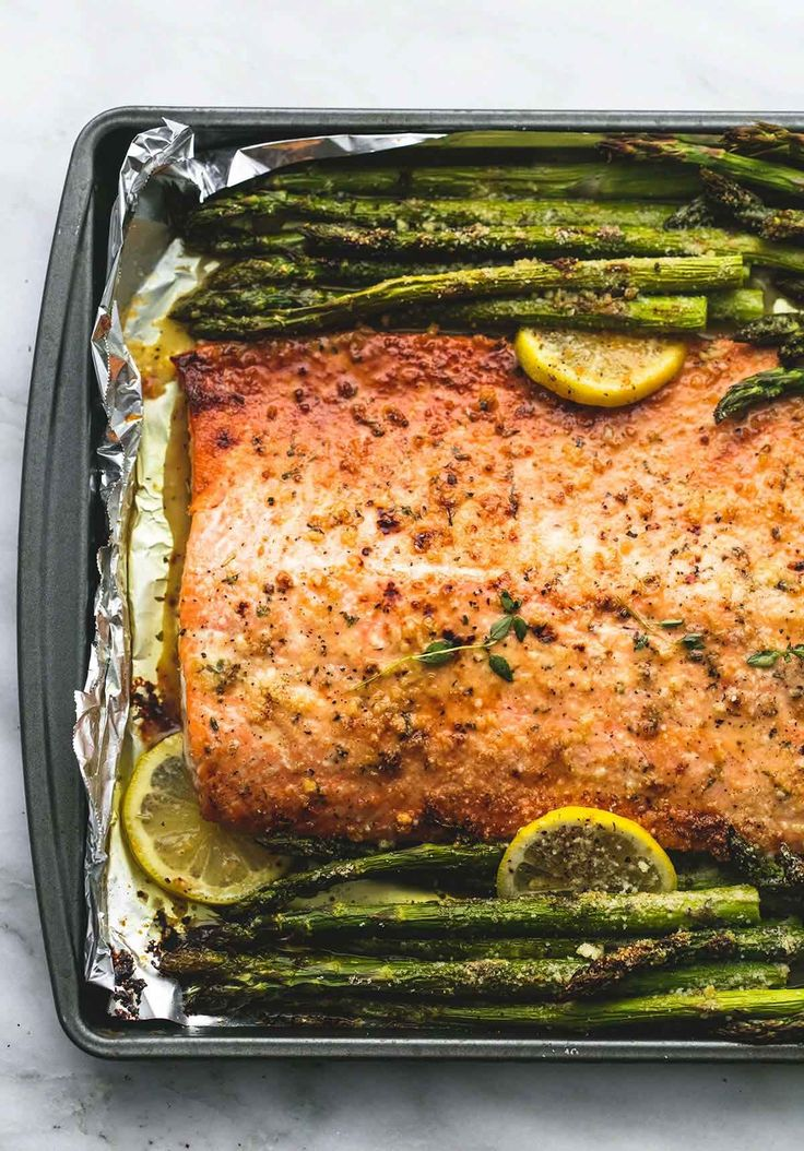 Baked Lemon Parmesan Salmon & Asparagus in Foil |  INGREDIENTS 1 large salmon fillet (or 4-6 single portion fillets) 1 pound asparagus spears, ends trimmed salt and pepper to taste ½ cup butter juice of 1 medium lemon, plus additional lemon slices for garnish (optional) 3 teaspoons minced garlic 1½ teaspoons Italian seasoning ½ cup grated parmesan cheese optional: fresh herbs for topping