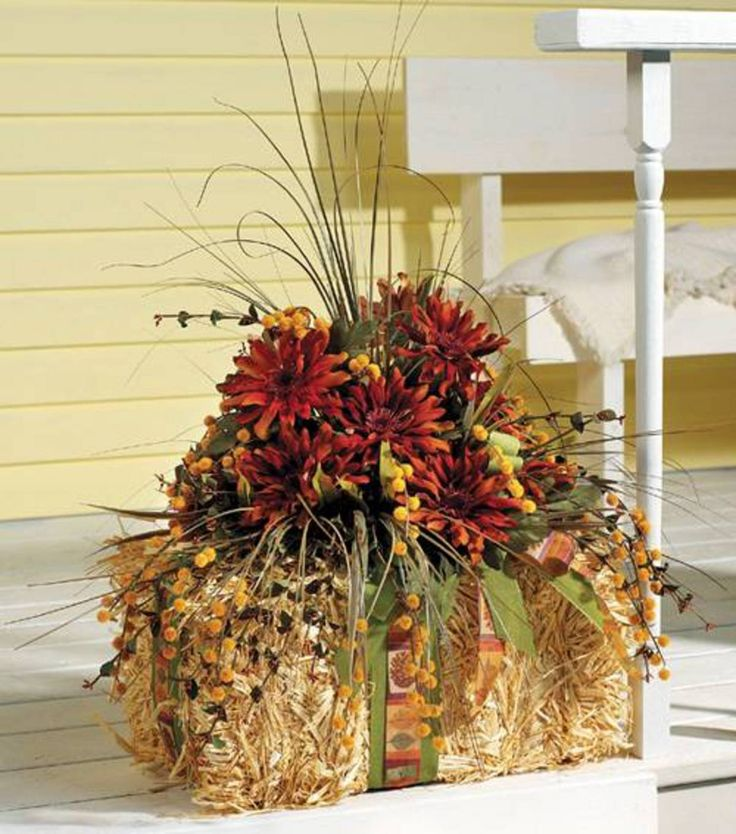 A fall flower arrangement with a barrel of hay adds warmth for Fall fake flower arrangement ideas