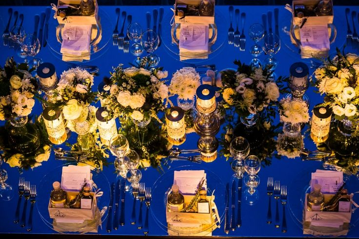 Reflections filling the space:  mirror runners, crystal vases and crystal candles, clear sous plats and little customised wooden boxes complete the simple yet elegant setting of the wedding reception