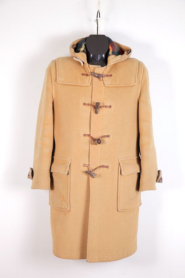Duffle Coat—A warm woolen coat of fingertip length with hood attached, having frogs of wood and rope. It came into use on the ski lift after WWII when surplus English Navy coats were made available to civilians. Worn by men and women and children, they are frequently of Tyrolean cloth with wooden toggles and hemp hoops.