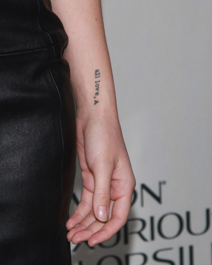 "The tattoo on Olivia Wilde's forearm reads ""all love, A""."