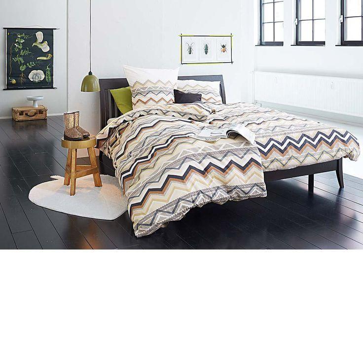 Dekorative Bettwäsche mit verschiedenen geometrischen Mustern in harmonischen Erdtönen.