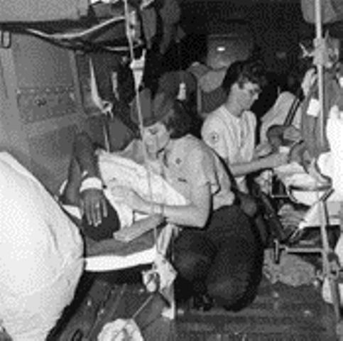 A U.S. Air Force flight nurse and a Red Cross nurse attend to the needs of American wounded prior to their aeromedical evacuation from Tan Son Nhut Air Base in the Republic of Vietnam. The wounded personnel are already aboard the Air Force C-141 which will take them on a direct flight from Vietnam to bases in the United States near specialized military medical facilities.