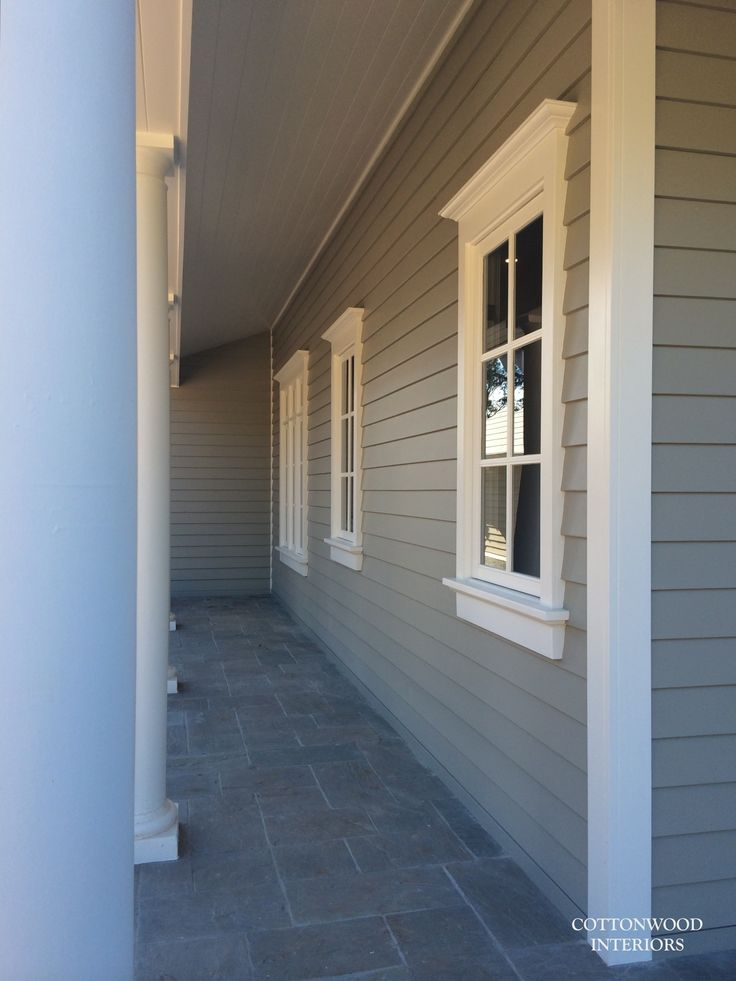 Grey exterior timber siding, white french windows, gray stone pavers in roman pattern | Cottonwood Interiors