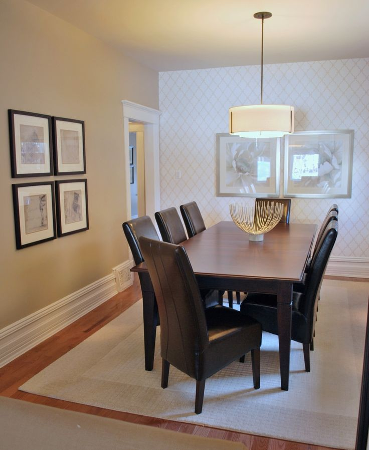 The contrast of the light walls and area carpet seems to illuminate the dark wood furniture in this dining room. The double barrelled pendent light with it's oil rubbed bronze finish helps to ground the space.