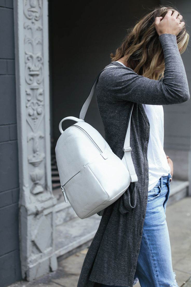 travel outfit white leather backpack and gray cardigan
