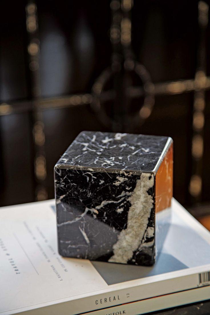 Detalle de la mesa en el living de un tríplex. Sobre ella, libros y un cubo de mármol Negromarquina de VK Home.