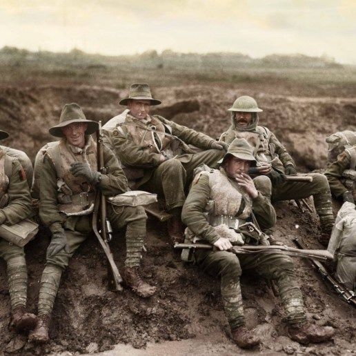 Unidentified men of the Australian 57th Battalion, 5th Division enjoying a smoke and rest by the side of the Montauban road, near Mametz, France, while en-route to the trenches. Most of the men are wearing sheepskin vests and woollen gloves, and are carrying full kit and .303 Lee Enfield rifles, December 1916.