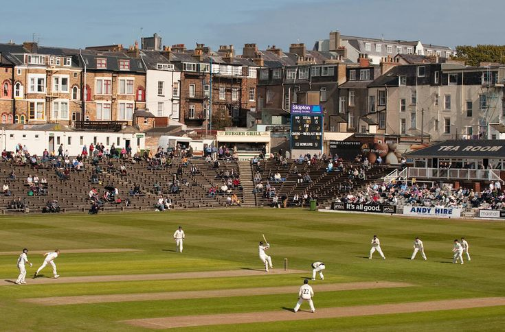 """North Marine Road Ground, formerly known as Queen's, is a cricket ground in Scarborough, North Yorkshire, England. It is the home of Scarborough Cricket Club which hosts the Scarborough Cricket Festival and the Yorkshire County Cricket Club plays a series of fixtures in the second half of the season each year. The current capacity is 11,500, while its record attendance is the 22,946. The two """"ends"""" are known as the Pavilion End and the Trafalgar Square End."""