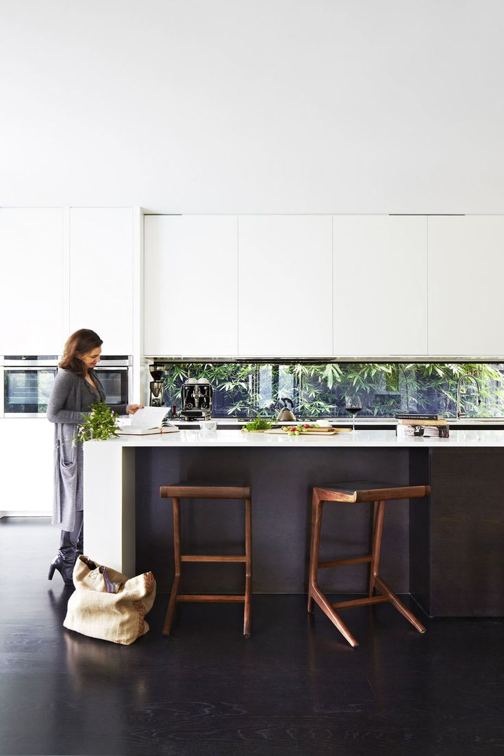 "Kylie at the long Corian benchtop, which affords her ample working space. To the right of the bench is a concealed butler's pantry. ""With the amount of entertaining we do, it's wonderful to have a designated place for mess,"" she says. Stools, Clickon Furniture. Flooring, American oak with a black japan finish. Australian House & Garden"