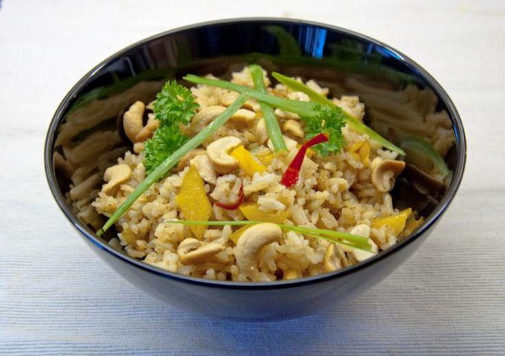 Thaise gebakken rijst met kip. Ingrediënten:  • 350-400 gr rijst  • 250 gr kipfilet  • 3 lente-uitjes of 1 ui  • 3 el zonnebloemolie  • 2 el vissaus  • 2 el (palm-)suiker  • 2 paprika's  • 1 el citroensap  • 50 gr cashewnoten  • 1 el sojasaus  • 1 el currypasta, vervang evt. door 1 tl sambal  • 3 tenen knoflook of 1 tl knoflookpoeder  • 1 rode peper of 1 tl cayennepeper  • 3 cm gember of 2 tl gemberpoeder  • 1 tl citroengras  • schijfjes komkommer en verse peterselie/koriander ter garnering