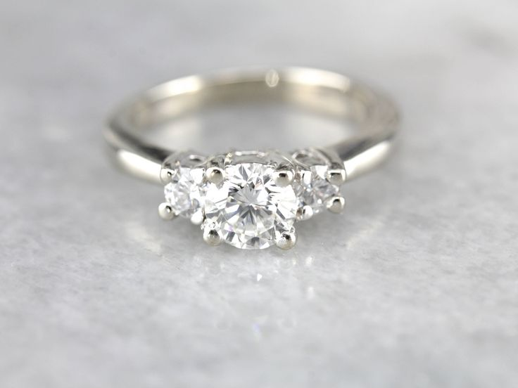 This three stone diamond ring packs a big visual impact for all of its balanced profile. The 14K white gold is perfectly designed; sleek, minimalist and polished on the finger. The classic three stone style here has been executed here with an ever-so-slightly larger center stone, giving the diamonds a subtle flowing, tapering look! Crafted to be worn for a lifetime, this can be worn alone with ease and will look lovely alongside a wide variety of bands. Metal: 14K White Gold Gem: Diamond .62…