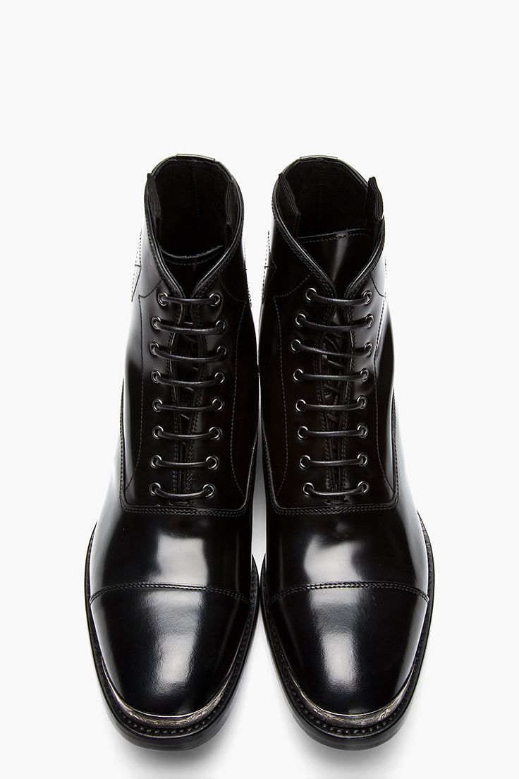ALEXANDER MCQUEEN //  Black leather metal-trimmed boots  32259M047003  Ankle-high buffed leather boots in black. Round cap toe trimmed in silver-tone etched metal at foxing. Tonal oxford-style lace up closure. Pull tabs at collar. Tonal stitching. Tonal leather sole. Upper, lining, sole: leather. Made in Italy.  $875 CAD
