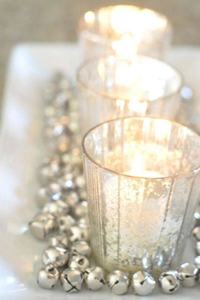 Create a chic holiday centerpiece by surrounding candles with silver jingle bells.: