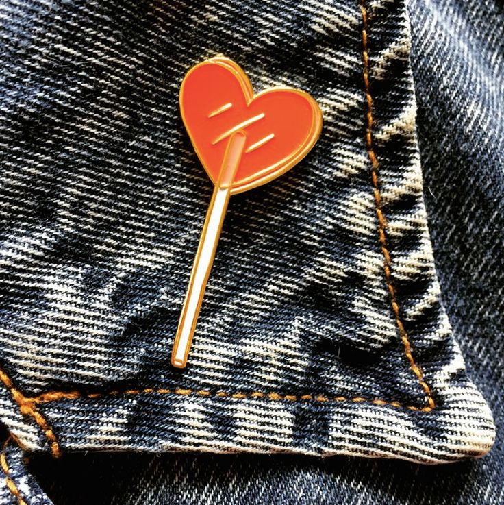 "Cute little heart lolli cloisonné pin made from my original illustration. Perfect for an accent on your lapel, backpack, or blouse.Approx 5"" x 2"", tri-colored enamel on gold tone metal with clasp back.THIS IS A PREORDER, IT WILL SHIP LATE MAY."