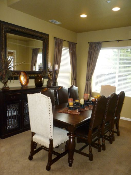 formal dining room large mirror above cabinet warm and