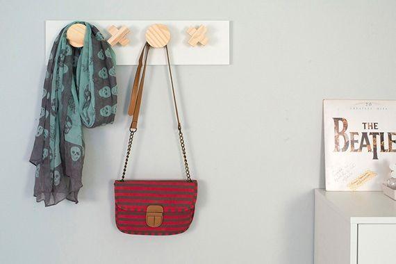 O cabideiro de parede aproveita o espaço vertical do quarto para organizar com praticidade. Bolsas, casacos e lenços podem ficar pendurados ali, para que fiquem ao alcance das mãos na hora de sair de casa.
