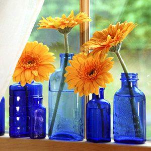 gerbera daisies in colored glass bottles along a windowsill
