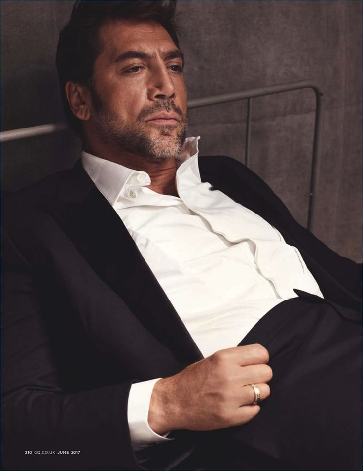 Relaxing, Javier Bardem dons a shirt and suit by Hermes.