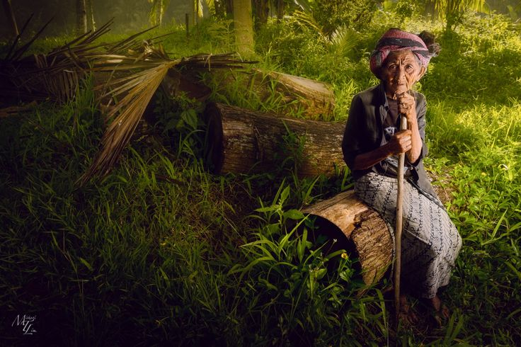 An elderly woman takes a seat on a log and rests in Ubud, Bali, Indonesia. by Michael Lim