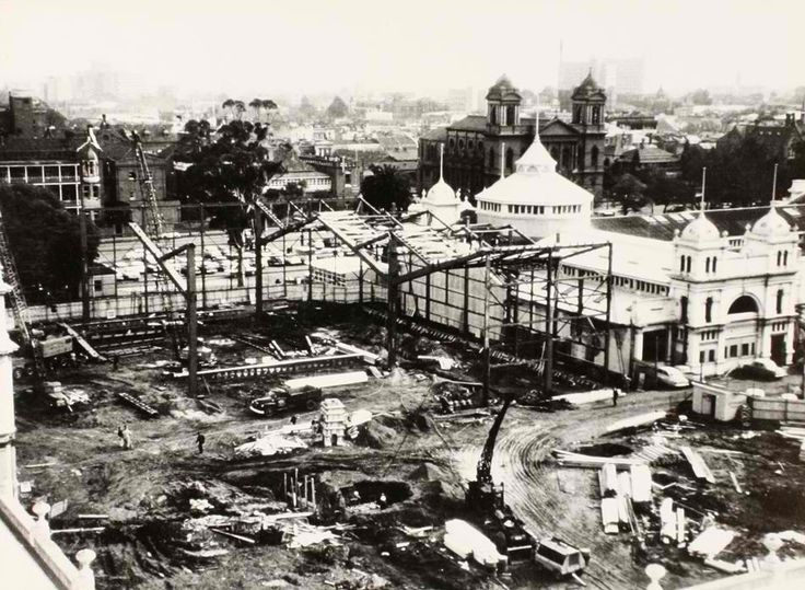 The construction of steel work for the new western annexe of the Exhibition Building, taken 8 June 1962. The photograph shows approximately half of the steel work erected for the new southern section. The old southern section was demolished between March and May 1962.