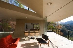 Em região montanhosa, casa tem laje flutuante sobre bloco de vidro e concreto